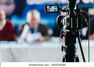 Professional digital camera recording presentation of a blurred speaker wearing suit, live streaming concept - Shutterstock ID 1403378186