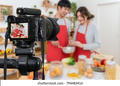 Professional digital Mirrorless camera with microphone recording video blog of Happy Asian Lover or couple cooking in the kitchen room, Camera for photographer or Video and Live Streaming concept