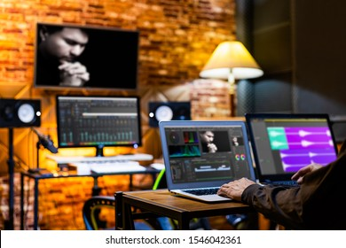 professional director, editor, producer editing movie footage and music score track on computer in digital editing, post production, broadcasting studio