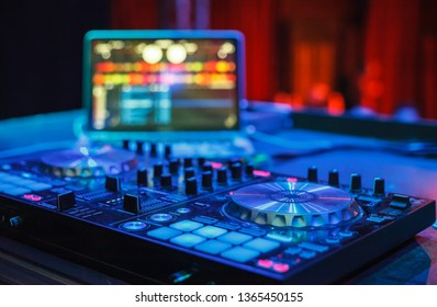 Professional disc jockey midi controller device and notebook with audio mixing software on festival stage in nightclub.Dj turntable player in bright neon blue lights on scene in music hall