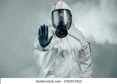 professional disinfector male show stop gesture to coronavirus, epidemic COVID-19. worker in gas-mask and specialist protective suit conducts disinfection in contaminated area