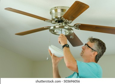 Professional or DIY do-it-yourself home owner doing ceiling fan repair work with the glass cover removed as he adjusts the fixture.