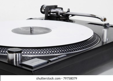 Professional DJ direct-drive turntable record player on white surface. Audio technology for sound recording studio,