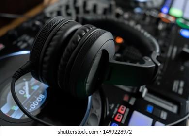 Professional dj headphones on audio mixer controller.Big black headset on sound mixing panel.Audio equipment for disc jockey