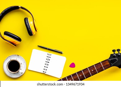 Professional dj instruments with headphones, guitar, notebook and coffee on yellow background top view mockup