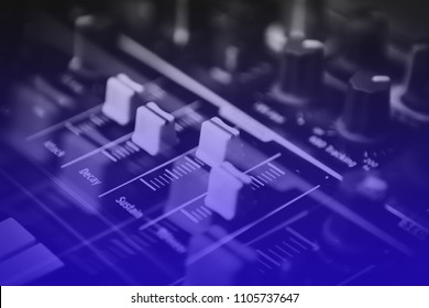Professional dj sound mixer controller panel in dark night club.Blue music background.Pro disc jockey audio equipment on concert stage.Electronic hardware for sound recording studio