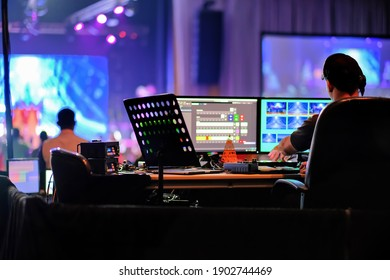 Professional DJ technical staff operating stage live broadcasting audio video mixer and computer monitoring console to switch camera scenes, music, sound, and lighting effects in holiday show event.