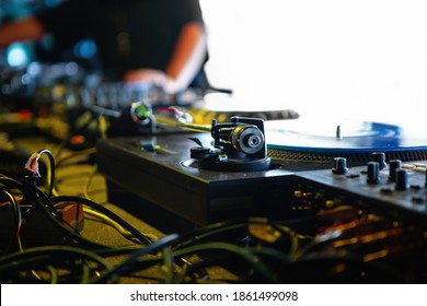 Professional dj turntable player on stage in night club.Turntables tonearm in focus.Retro analog audio equipment for disc jockey at musical festival.Hip hop battle djs setup set for live performance