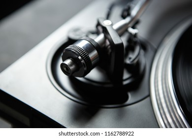 Professional dj turntables tone arm in close up. Adjust turn table player and play old analog vinyl records with music on party in night club.