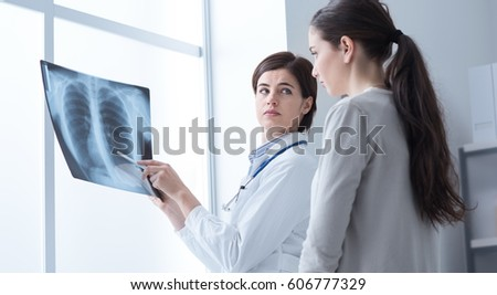 Professional doctor examining a patient's x-ray and pointing, medical exams and diagnostics concept