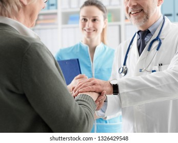 Professional doctor helping and supporting a senior patient, he is holding her hands, healthcare and geriatrics concept