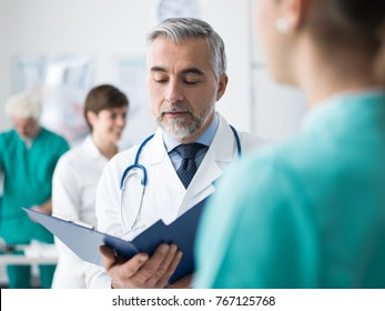 Professional doctor and medical staff working at the hospital, he is examining patient's medical records