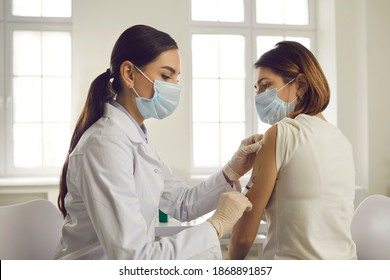 Professional doctor or nurse giving flu or COVID-19 injection to patient. Woman in medical face mask getting antiviral vaccine at hospital or health center during vaccination and immunization campaign - Shutterstock ID 1868891857