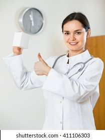 Professional doctor offering new medicine and smiling in clinic