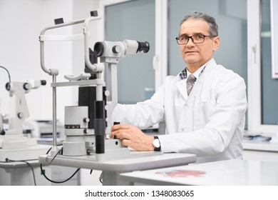 Professional doctor ophthalmologist sitting at table with special equipment slit lamp. Special device for examining eyesight of patients in medical clinic. Concept of health care and eye testing.