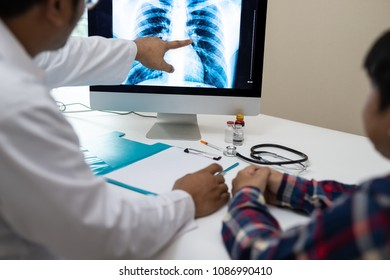Professional doctor and radiologist giving a consultation to his patient, He pointed to the results of x-ray at the computer screen.