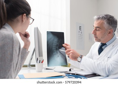 Professional doctor and radiologist giving a consultation to his patient, he is examining and x-ray image and pointing