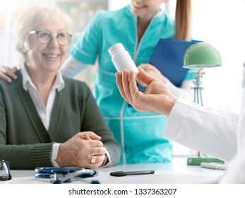 Professional doctor sitting at office desk and giving a prescription medicine to a smiling senior female patient, a nurse is holding her shoulder, medicine and healthcare concept