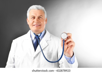 Professional doctor with stethoscope on grey background