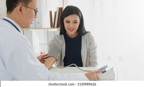 Professional doctor wearing white coat is checking woman patient with stethoscope and measure blood pressure in hospital background.Concept of health check in hospitals.