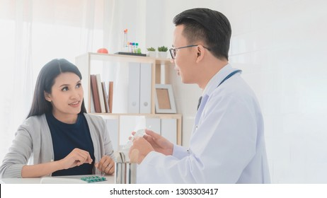 Professional doctor wearing white coat describe how to take medicine to woman patient in hospital background.Concept of disease treatment and health care in hospitals.