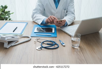 Professional doctor working at office desk, he is using a smartphone, healthcare and technology concept