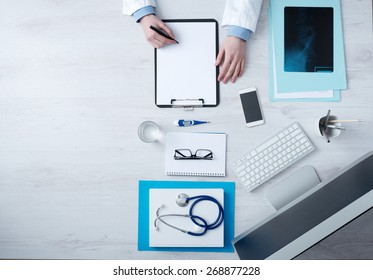 Professional doctor writing medical records on a clipboard with computer and medical equipment all around, desktop top view with copyspace