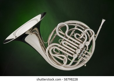 A professional double French horn isolated against a spotlight green background.