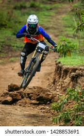 A professional down hill cyclist racer jumping and doing a swipe on his full suspension carbon bike