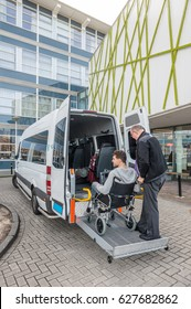 Professional driver assisting male passenger in wheelchair to board taxi outside building