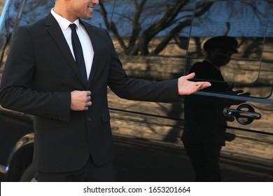 Professional driver near luxury car, closeup. Chauffeur service