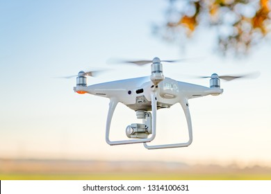 Professional drone with camera in flight. White drone
