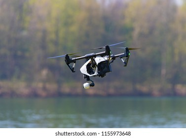 Professional drone with camera flying over a lake