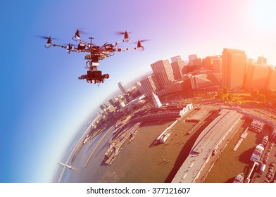 Professional drone with the cinema camera flying over San-Francisco pears and the financial district at the summer sunset. Toned photo with little planet effects.
