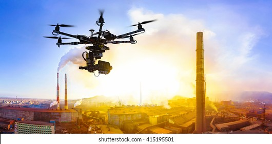 Professional drone flying over factory at sunset