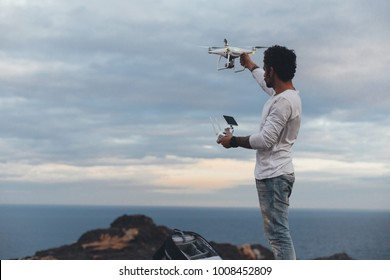 Professional drone pilot or stock photographer, prepares to fly high technology futuristic drone into air, sets up controls and remote connection. Ready to explore nature and cliffs from top