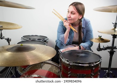 Professional drum set closeup. Beautiful young girl drummer with drumsticks playing drums and cymbals, on the live music rock concert or in recording studio. Female drummer.