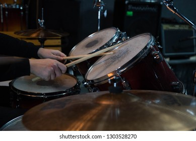 Professional drum set closeup. Man drummer with drumsticks playing drums and cymbals, on the live music rock concert or in recording studio