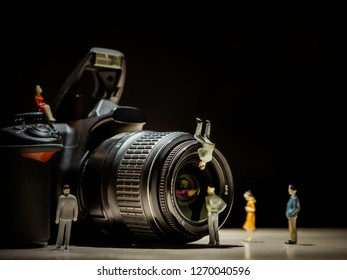 Professional DSLR camera and lens with black background. Small human figures standing in front of the camera and lens