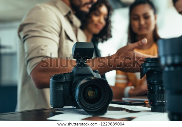 Professional DSLR camera and lens on the table with team of photographers discussing in the background. Photographer talking to his team during a photo shoot.
