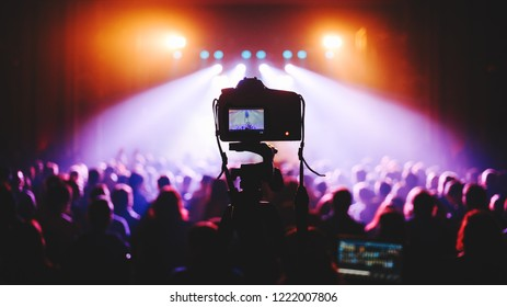 Professional dslr camera at music concert on a tripod recording performance on video. silhouettes of crowd in front of bright stage lights.