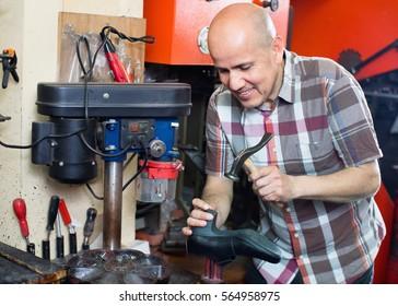 Professional efficient smiling  shoemaker heeling footwear on machine in workshop