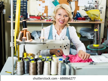 Professional elderly glad woman tailor working on sewing machine at studio