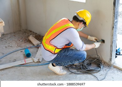 Professional electrician installer and working with cable on the construction site. construction site cabling