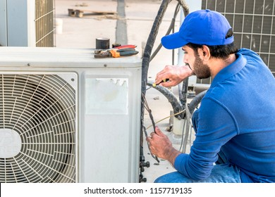a professional electrician man is fixing the heavy air conditioner by his tools on the roof top and wearing blue color of uniform and head cap