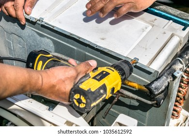 a professional electrician man is fixing the screw by auto screw driver machine into the window air conditioner after the cleaning