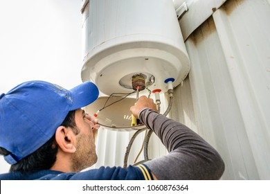 a professional electrician man is fixing a water heater at the roof top and wearing blue uniform and cap