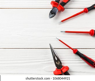 Professional electrician tools on white wooden texture. Electric equipment background.