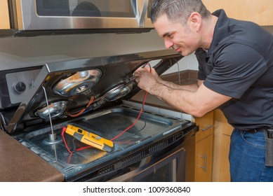Professional electrician troubleshooting an electric stove top burner with a multi-meter. Taken inside of an apartment.