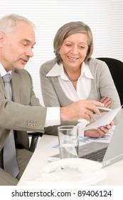 Professional elegant happy senior businesswoman looking graphs with man colleague